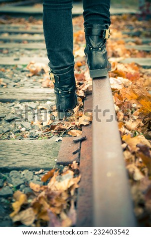 Black leather boots along old railroad tracks.  Vintage toned image.  - stock photo