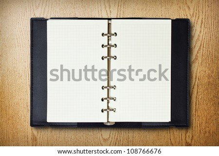 Black leather cover of binder notebook on wood background - stock photo