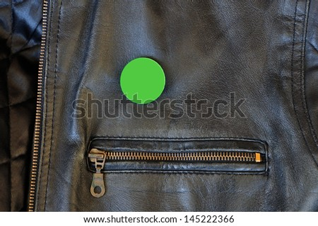 Black leather jacket with zipper and blank pin badge to add your own text or logo. - stock photo