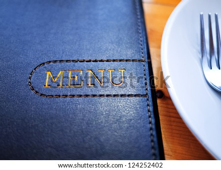 Black Leather Menu with White Plate on wood table.