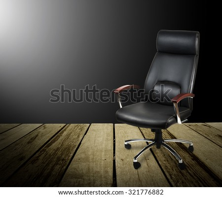 Black leather office chair on wood floor,dark background