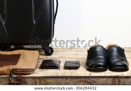 Black leather shoes, wallet,mobile smart phone and  luggage travel bag on the wooden table