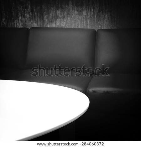 Black leather sofa and white coffee table. - stock photo