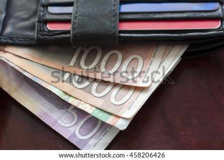 Black leather wallet full with Serbian diners lying on dark red wooden background.