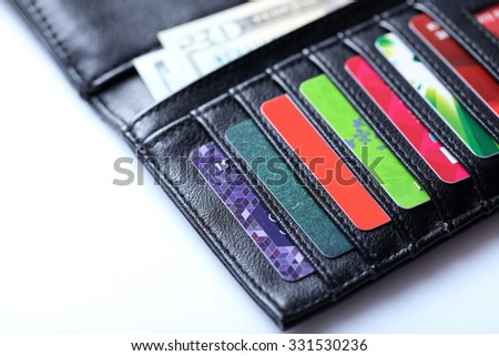 Black leather wallet with colourful credit cards and money on white background, close up