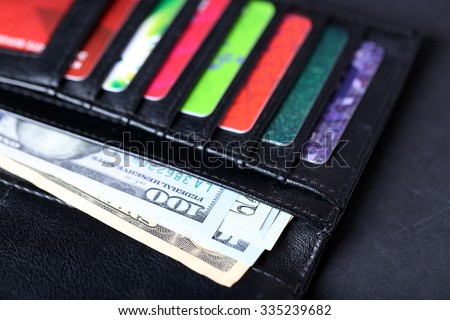 Black leather wallet with credit cards and money, close up