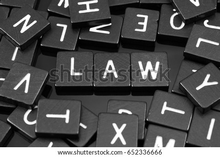 "Black letter tiles spelling the word ""law"""