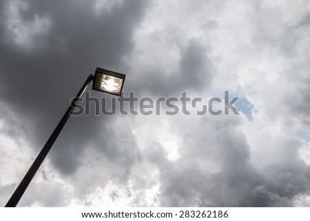 Black light pole standing alone in the storm - stock photo