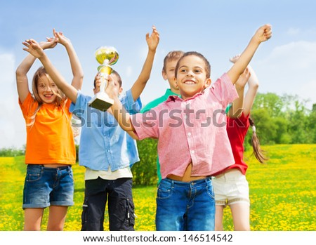 Black little boy standing with cup as his team wins - stock photo