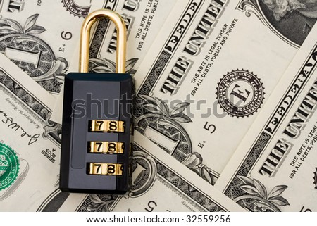 Black lock sitting on a dollar bill background, investment security