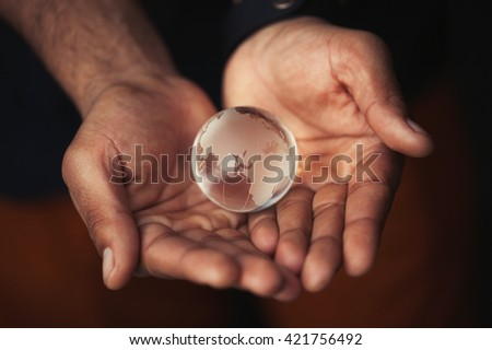 Black male hands holding glass Earth model. Concept for planet care, ecology and environment. Macro close up, focus on globe - stock photo