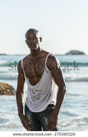 Black male model, ripping his white vest shirt - stock photo