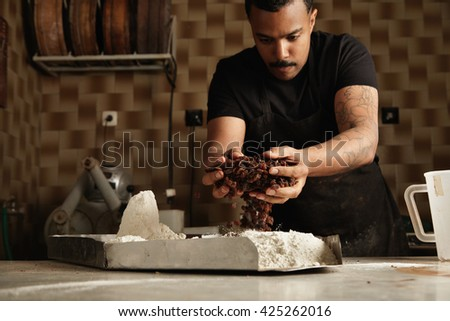 Black man chief cooks cakes. Baker adds some dry fruits in flour inside metallic pot to mix it and make cake batter in his professional artisan confectionery - stock photo
