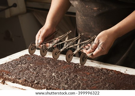 Black man chief use professional vintage separator to split chocolate cake on equal portions before packaging, artisan cooking process - stock photo