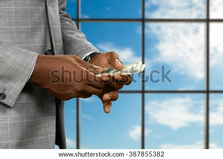 Black man counts office salary. Businessman counts money near window. It's never enough. Always chasing success. - stock photo