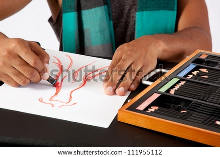 Black man drawing with a pastel, creating fashion dresses, - stock photo