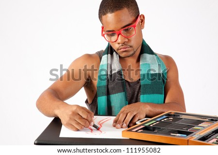 Black man drawing with a pastel, creating fashion dresses, wearing glasses and a scarf - stock photo