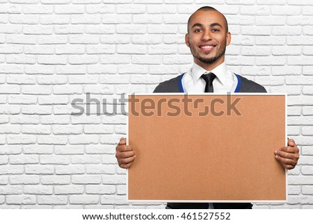 black man holding a cork board