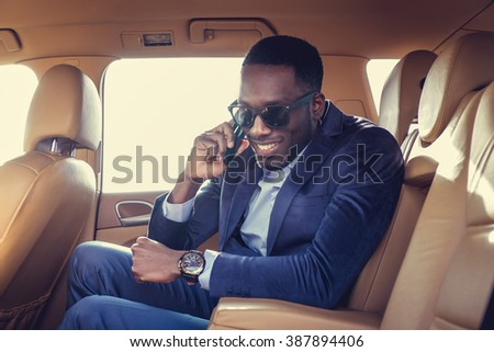 Black man in the car talking on smartphone. - stock photo