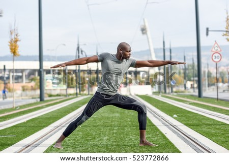 Black man practicing yoga in urban background. African male doing workout outdoors.