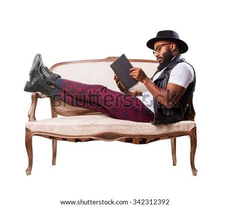 black man reading on a sofa - stock photo