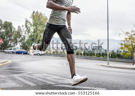 Black man running outdoors in urban road listening to music with white headphones. Young male exercising with city scape at the background.