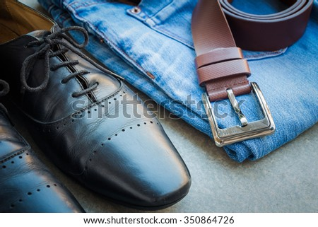 Black man's shoes and outfit with blue jean and brown belt on gray background, selective focus