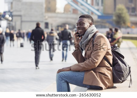 Black man talking on mobile phone in London. He is seated on a concrete bench, on background there are a lot of blurred persons and the Tower Bridge - stock photo