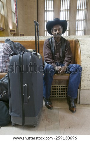 Black man with bags, cowboy hat and cowboy shoes waiting for train at 30th Street Station, AMTRAK Train Station in Philadelphia, PA - stock photo