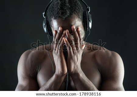 Black man with ear-phones covering his face while laughing against dark background.  - stock photo