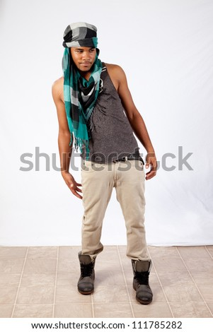 Black man with his head in a turban like an Arab or Mid Eastern man, looking at the camera and leaning to the left - stock photo