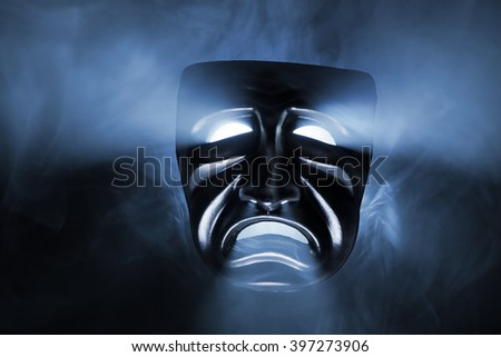 Black mask with light coming from its eyes and mouth.
