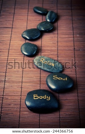 Black massage stones with words body, soul and relax on the brown mat - stock photo