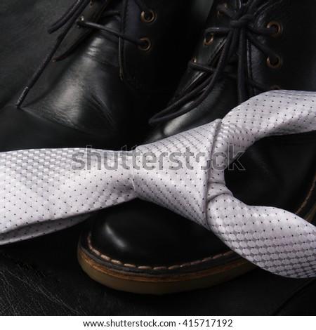 Black men's shoes and white luxury tie on dark background. - stock photo