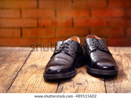 black men's shoes on wooden background