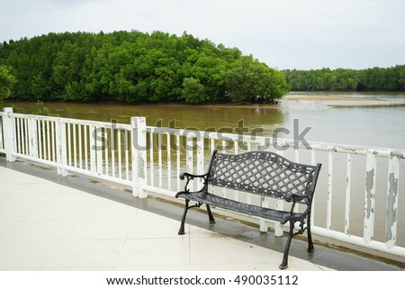 Black metal chair  near white fence with background green mangrove forest and river at public park.