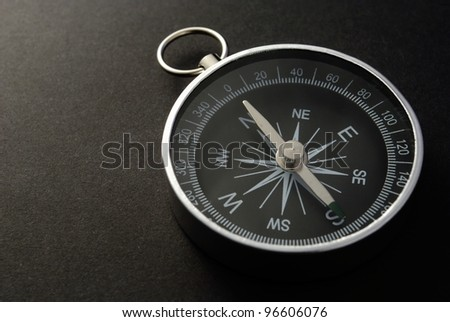 black metal compass on a black background