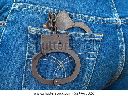 Black metal handcuffs in back jeans pocket