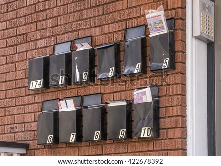 Black metal mailboxes,full of mail, hang on a red brick wall outside an apartment building. - stock photo