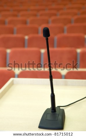 Black microphone is standing against auditorium with red chairs - stock photo