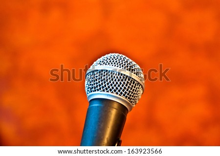 Black microphone on an orange background - stock photo