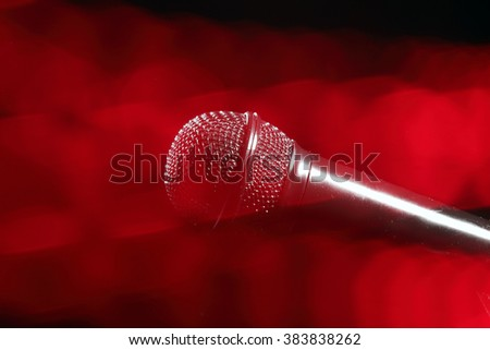 Black microphone with red rays of light