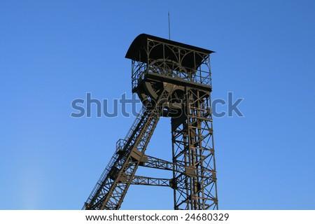 Black mining tower on blue background - stock photo