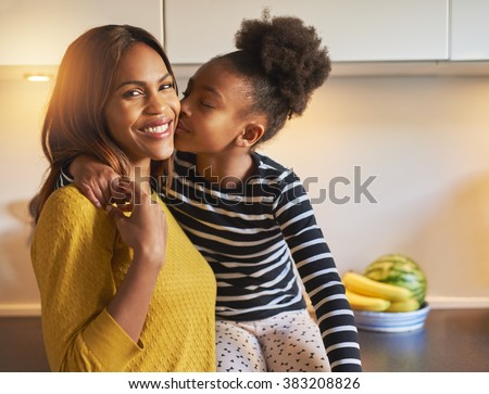 Black mom and daughter loving each other woman smiling at camera - stock photo