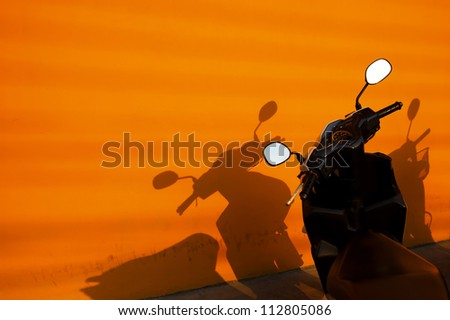 Black motorbike parked near an orange wall - stock photo