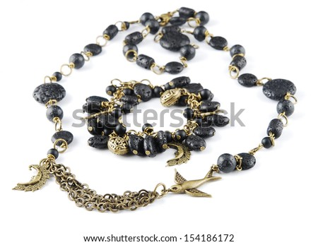 Black necklace and bracelet on white 	  - stock photo
