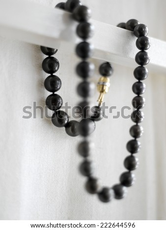 Black necklace hanging against white background