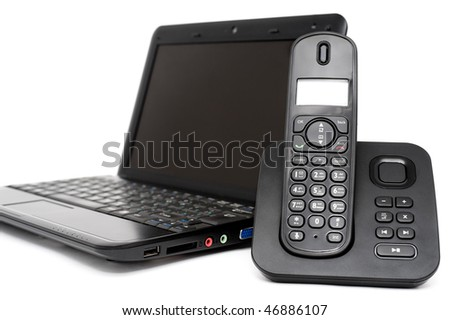 black netbook and decked telephone over white background