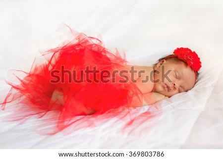 Black newborn baby wearing red tutu skirt and headband sleeping on the white bed. - stock photo