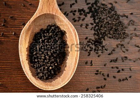 Black Nigella Sativa dry seeds portion on wooden spoon and spilled around food macro, Black cumin raw spice heap in day light, horizontal orientation, nobody. Polish name czarnuszka siewna. - stock photo